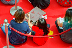 Girl making a drawing for Joseph Schooling, the Singapore's first Olympic gold medalist, at Raffles City. August 18, 2016. Crowd waiting with colourful banners stock photo