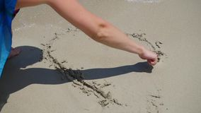 The girl is making a drawing on the sand. The sea wave is washing away the pattern on the sand on a sunny day stock video footage