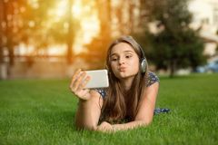 Girl making duck face outdoors lying down royalty free stock photography