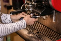 Girl making espresso coffee on a professional machine in the bar royalty free stock images