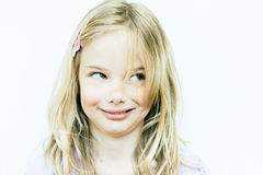 Girl making face. Little blond girl making a silly expression on pale background Stock Photography