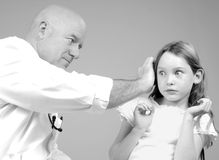 Girl Making Face During Exam. Young girl with funny expression during ear exam as part of checkup stock photography