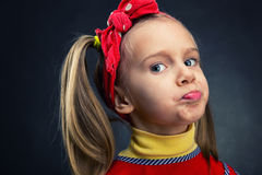Girl making faces. Cute little girl making faces over grey background Royalty Free Stock Photography
