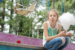 Girl making faces while eating cotton candy Stock Photography