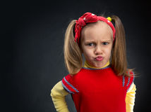 Girl making faces. Funny little girl making faces over grey background Royalty Free Stock Images