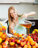 Girl making fresh beverages with fruits at home kitchen. Positive blonde long-haired girl making fresh beverages with fruits at home kitchen Stock Photography