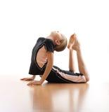 Girl making frog on floor in bodysuit Royalty Free Stock Image