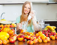 Girl making fruits cocktail with blender Stock Images