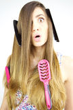 Girl making funny faces having trouble with long hair. Cute girl making funny faces with brushes in hand and hair Royalty Free Stock Image