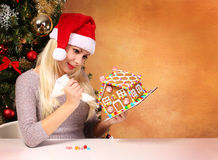 Girl making gingerbread house. Young woman with Santa Hat Royalty Free Stock Image