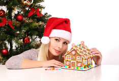 Girl making gingerbread house. Young woman with Santa Hat Stock Photo