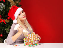 Girl making gingerbread house. Young woman with Santa Hat Royalty Free Stock Photos