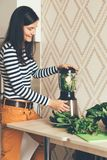 Girl making green smoothie in a blender royalty free stock image