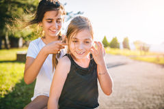 Girl making hair braid. To her sister in park Stock Photo