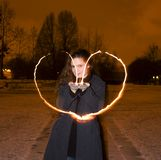 Girl making heart with candle light. Photo of girl that is making heart form with candles Stock Photos