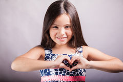 Girl making a heart with her hands. Cute little girl in a dress making a heart with her hands and smiling on a white background Royalty Free Stock Photography
