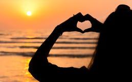 Girl making heart shape at seaside Royalty Free Stock Photo