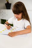 Girl making her homework. Young caucasian girl doing her homework while sitting at table Royalty Free Stock Photo