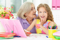 Girl making homework with granny Stock Photos