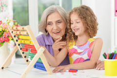 Girl making homework with granny Stock Photo