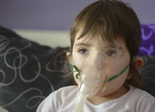 Girl making inhalation with mask on her face Stock Images