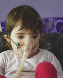 Girl making inhalation with mask on her face Royalty Free Stock Image