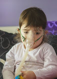 Girl making inhalation with mask on her face Stock Photography