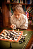 Girl making move on chess board Royalty Free Stock Photos