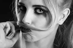 Girl making mustache. Fun blond girl making fake mustache from her hair, monochrome image Royalty Free Stock Photography