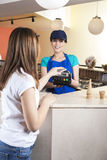 Girl Making NFC Payment On Mobile Phone While Waitress Smiling Stock Image