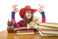 Girl making the ok sign sitting at the table with stack of books Royalty Free Stock Image