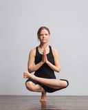 Girl making one foot balance yoga pose. royalty free stock image