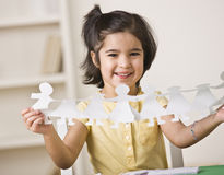 Girl Making Paper Dolls Stock Photo