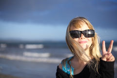 Girl making peace sign. A little girl in sunglasses making the peace sign royalty free stock photo
