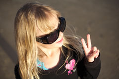 Girl making peace sign. A little girl in sunglasses making the peace sign stock photography