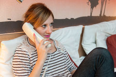 Girl Making a Phone Call. Young pretty girl using a phone in her bedroom, or in a hotel room Royalty Free Stock Photos