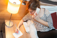 Girl Making a Phone Call. Young pretty girl using a phone and writing a note in her bedroom, or in a hotel room Stock Images