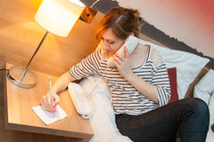 Girl Making a Phone Call. Young pretty girl using a phone and writing a note in her bedroom, or in a hotel room Stock Image