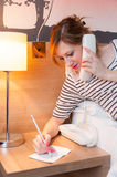 Girl Making a Phone Call. Young pretty girl using a phone and writing a note in her bedroom, or in a hotel room Stock Photo
