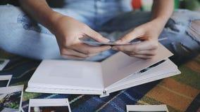 Girl making a photo album woman lies at sofa and recall the memories