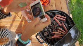 Girl making photo of grill sausages and tomatoes. Vegan bbq party. HD slowmotion