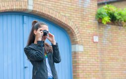 Girl making photo of historical building with retro camera on city street stock photography