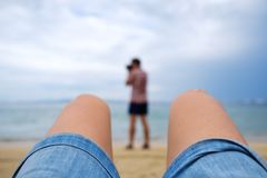 Girl making a photo of photographer on sandy beach. Stock Photography