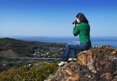 Girl making photo on the rock Stock Photo