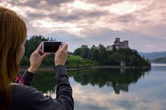 Girl making a photo shoot of castle niedzica stock images