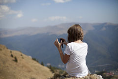 Girl making photos. Teenager woman creating images with mobile Stock Photography