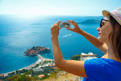Girl  making photos by the smartphone island of Sveti Stefan, Mo Royalty Free Stock Photography