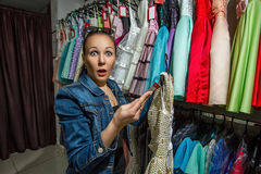 Girl making a purchase of a dress royalty free stock photos