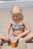Girl Making Sand Castles at Beach. Five year old blond Girl Making Sand Castles at Beach, bathing suit, bucket, beach sand, natural light Stock Images
