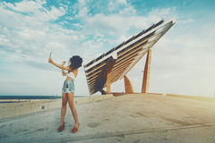 Girl is making seifie in front of solar power station. Woman is shooting selfie on touch pad in front of huge solar panel, curly girl is making photo of herself Stock Image